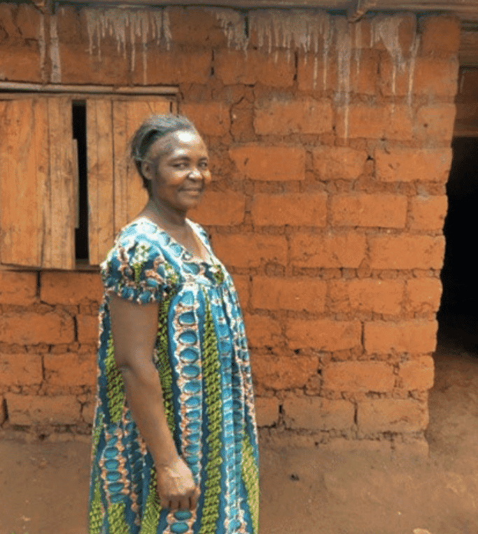 Jeannette stands proudly in front of her home that she built with the money saved from selling her farm's outputs.