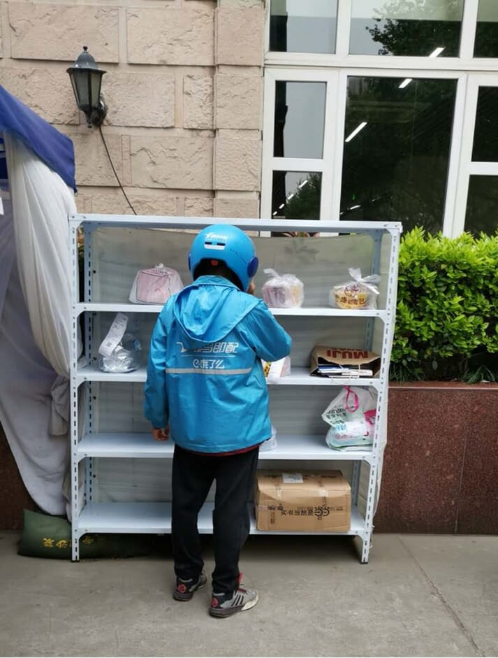 A delivery driver picks up food parcels for delivery during the coronavirus outbreak in China