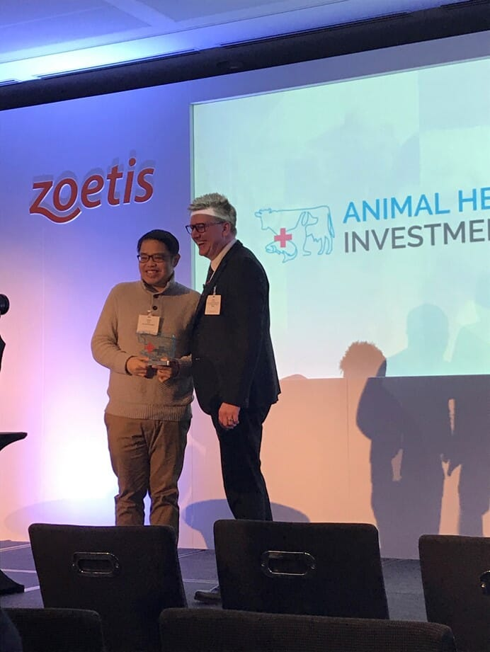 Zoetis Senior Vice President Jamie Brannan presents Amado Guloy, CEO and founder of Rex Animal Health, with the 2019 Animal Health Innovation Award.