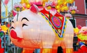 A handmade paper lantern procession through the suburbs feature a smiling pig – a symbol of wealth and prosperity. thumbnail