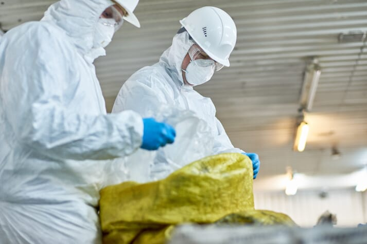 two people dressed in biosecure white overalls collect hazardous and infected materials from a barn