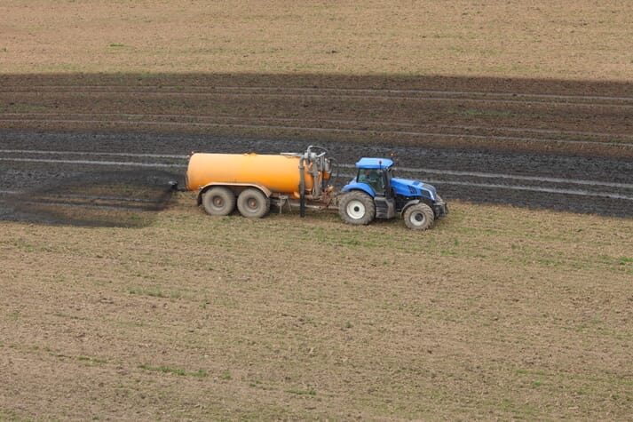 tractor spreads manure on a crop field
