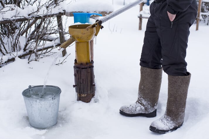 water pump being used to fill up a bucket in the snow