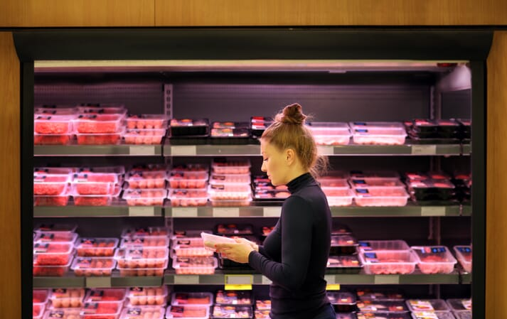 woman reads packaging of meat in a supermarket
