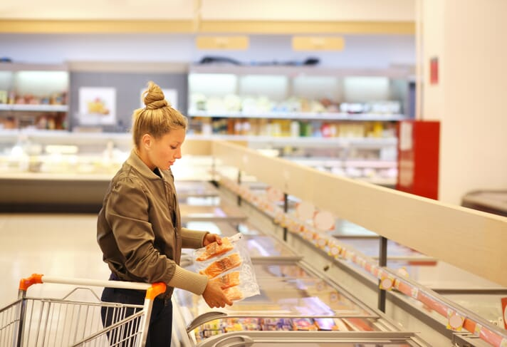 lady assesses the selection of meat products in a supermarket freezer
