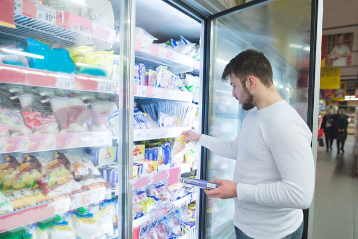 Male supermarket shopper looking at lunchmeat in a refrigerated case
