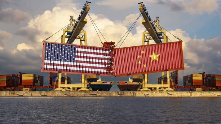 Two shipping containers with the US and Chinese flags being pushed together