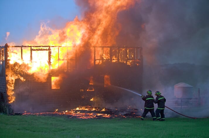 firefighters trying to control a barn fire