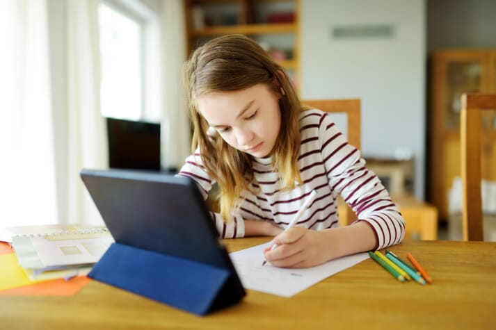 young girl doing distance learning with an ipad
