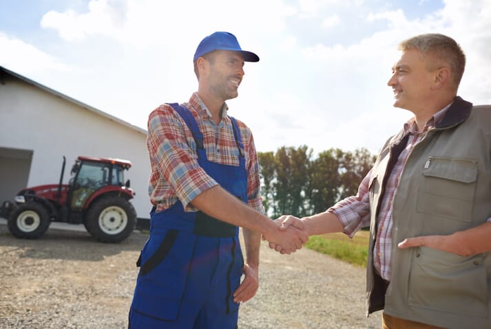 two farm staff shaking hands