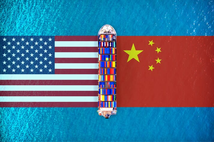 A container ship in between the US and Chinese flags