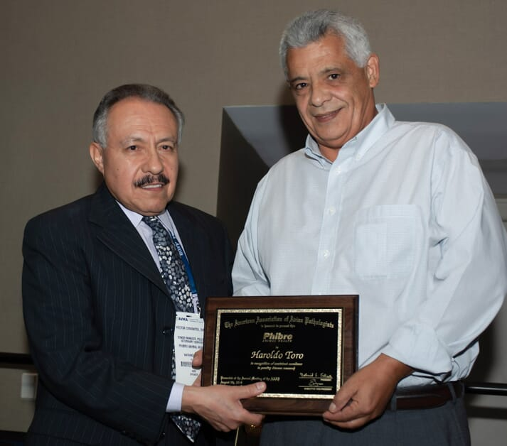 Dr. Haroldo Toro, right, Auburn University professor of avian diseases, receives the American Association of Avian Pathologists' Phibro Animal Health Excellence in Poultry Research Award from Dr. Hector Cervantes, AAAP past president and Phibro representative.