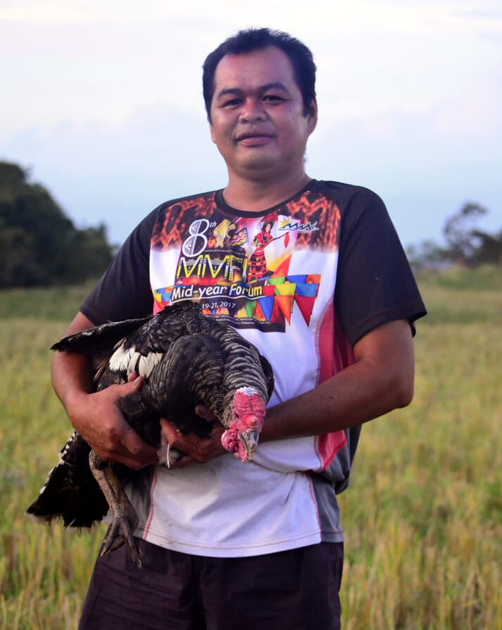 a man stands in a field and holds a turkey