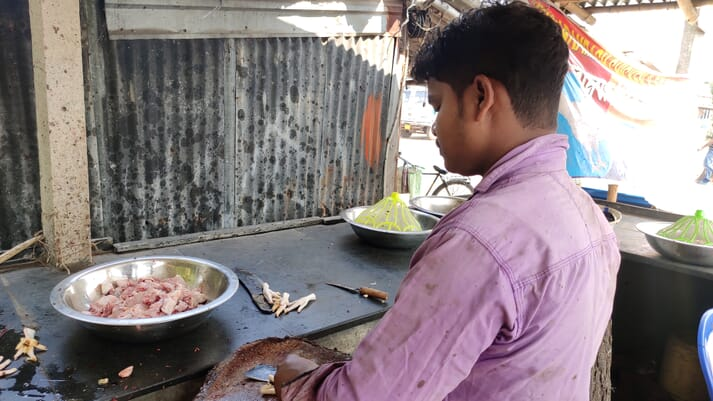 a man wearing a pink shirt looks at a bowl full of chicken meat
