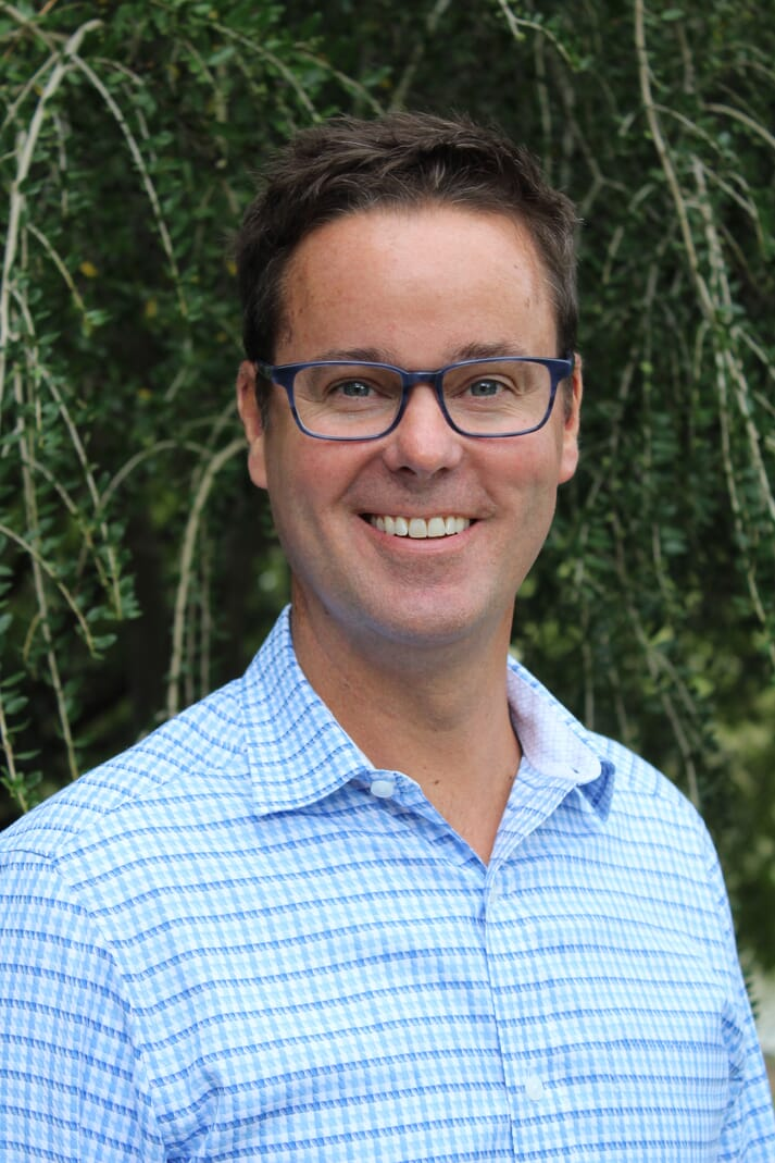 a man with glasses and a blue shirt with short brown hair smiles at the camera