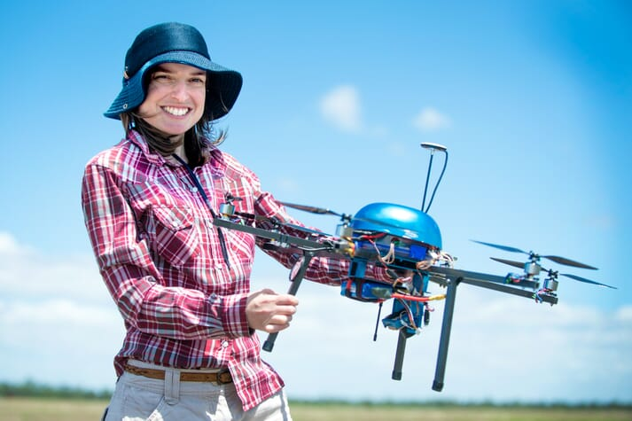 a woman holds a drone
