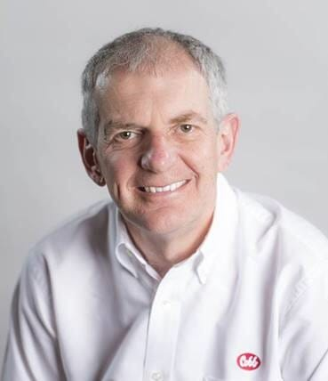 a haedshot of a man in a white shirt smiling; the red Cobb logo is on the shirt