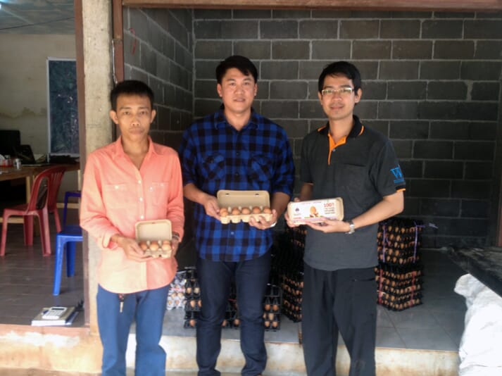 three men standing and holding eggs