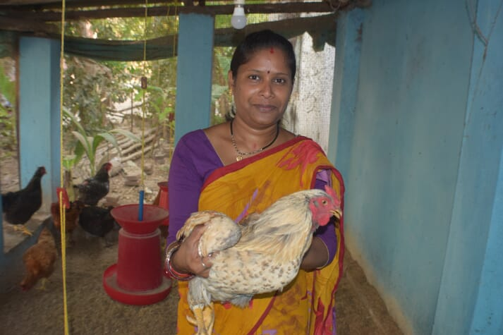 a women holds a chicken and smiles