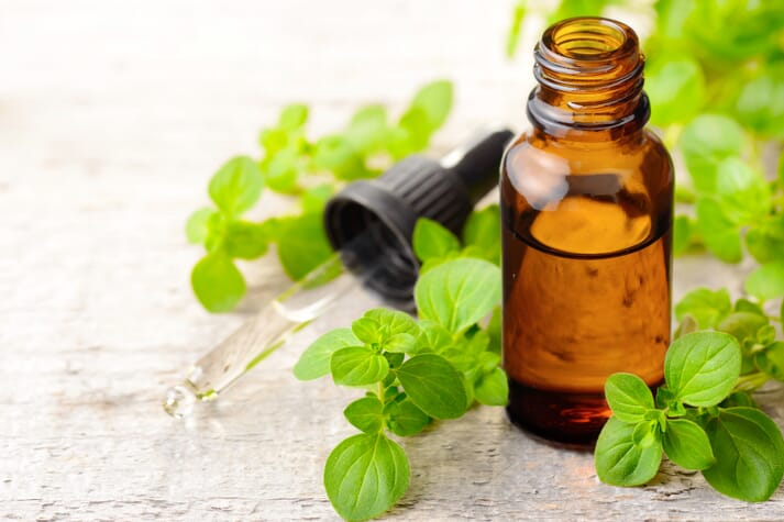 a small brown bottle of oil with oregano leaves around it