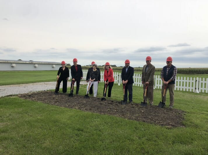 seven people with spades posing for photograph at ceremonial digging of the foundations.