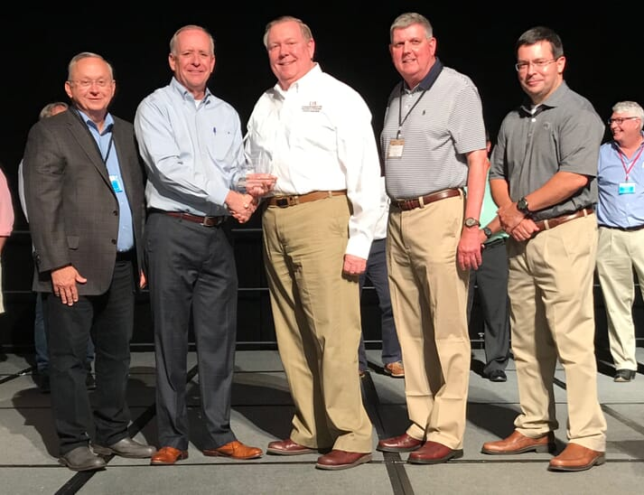 Marvin Childers, president of The Poultry Federation, shakes hands with John Marcy (white shirt), as Marcy was named the Industry Leader of the Year by TPF for 2019