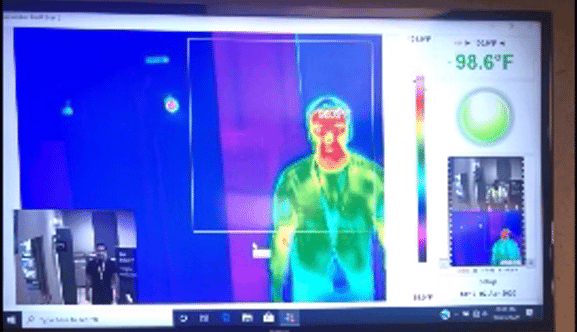a man walks between two yellow posts and a computer display shows his body temperature