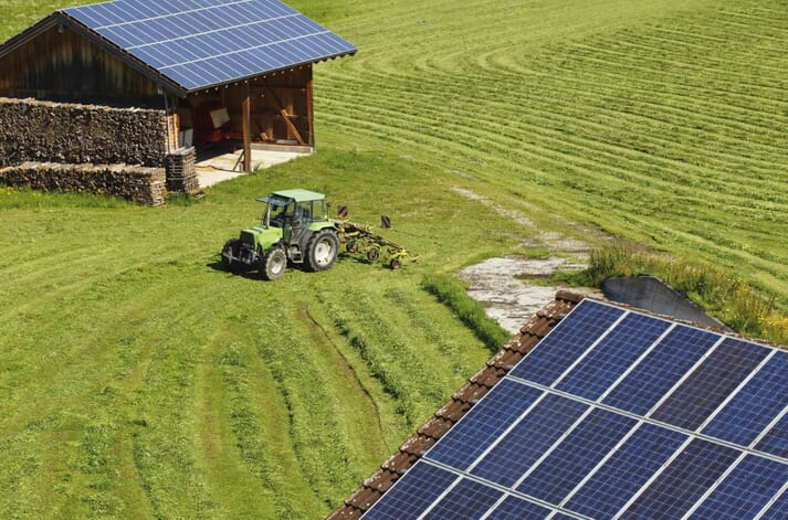a farm in a field by a barn with solar panels on