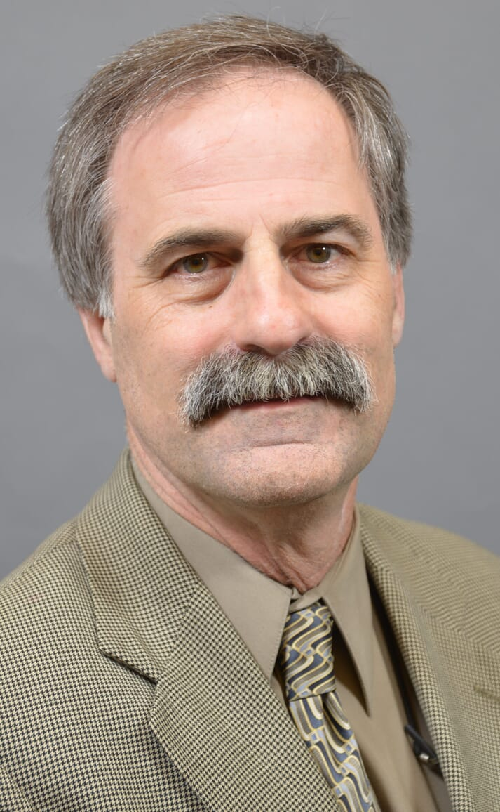 a man with a moustache smiling