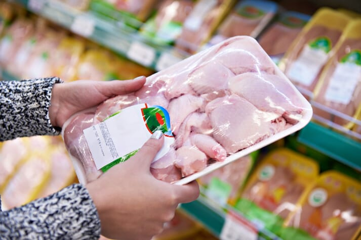 supermarket shopper holding a package of chicken thighs