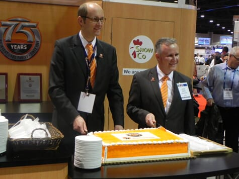Bernd Meerphol, Big Dutchman CEO (l) and Clovis Rayzel, President of Big Dutchman, Inc (r), cut the anniversary cake during the 2013 IPPE show in Atlanta