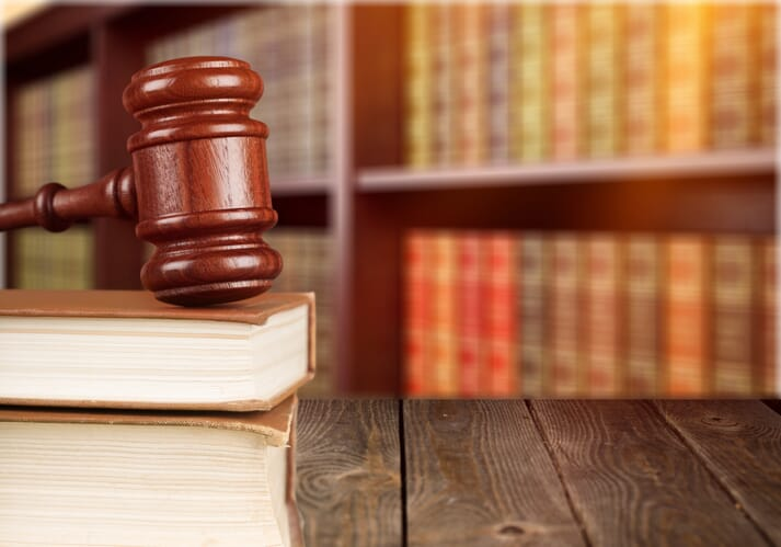 Gavel and textbooks on a wooden table